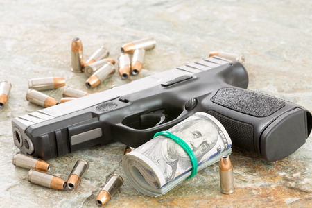 criminality: Conceptual image of a handgun with a roll of money surrounded by scattered bullets and cartridges on an old weathered wooden surface