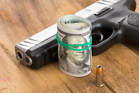 Handgun with a roll of 100 dollar bills and a single bullet lying on a wooden surface with the barrel and muzzle towards the camera