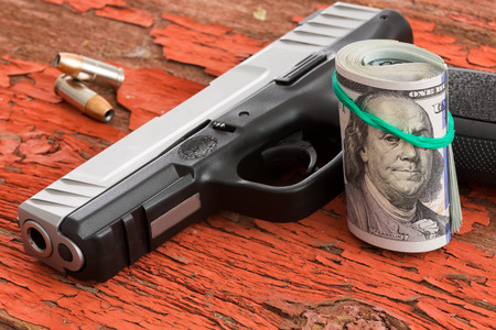 rubber band: Gun with a roll of 100 dollar banknotes and two bullets lying on a grungy wooden surface with red peeling paint conceptual of crime, robbery, coercion, bribe or mob protection money Stock Photo