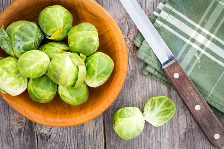 Preparing brussels sprouts for the evening meal with an overhead view of fresh healthy sprouts in a wooden dish alongside a kitchen knife and napkin on old weathered wooden boards photo