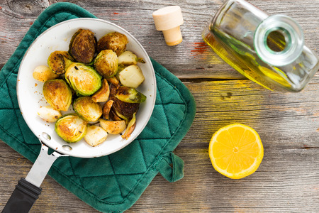 country kitchen: Delicious sauteed brussels sprouts with olive oil and fresh lemon for a tangy zesty flavour in a saucepan on a rustic tabletop in a country kitchen, overhead view Stock Photo