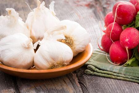 pungent: Close up vista di nuove teste d'aglio interi sani per un condimento piccante aromatico usato in cucina con un mazzo di ravanelli rossi croccanti su vecchie tavole di legno