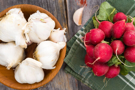 potherb: Overhead view of whole bulbs of fresh garlic in a wooden bowl with a bunch of farm fresh radishes ready to be used in preparing a healthy meal