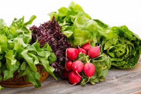 copyspace와 흰색 배경 위에 잎이 많은 녹색 양상추와 선명 후추 무의 무리의 여러 종류와 오래 된 풍 나무 판에 표시 건강 한 신선한 샐러드 재료