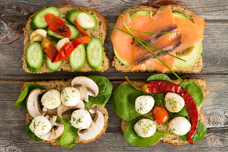 'baby spinach': Four delicious open wholewheat sandwiches on a wooden picnic table topped with smoked salmon, avocado, mushrooms, cucumber , baby spinach and mozzarella cheese