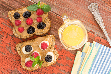 Overhead view of snacks on whole grain brown bread with fresh berries at a healthy country picnic laid out on a grungy old table with peeling paint alongside a jug of freshly squeezed orange juice