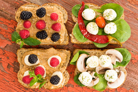 baby spinach: Healthy rustic picnic lunch with an assortment of wholewheat sandwiches topped with blackberries and raspberries, cheese, baby spinach, chili pepper and mushrooms, overhead view on a grungy wood table
