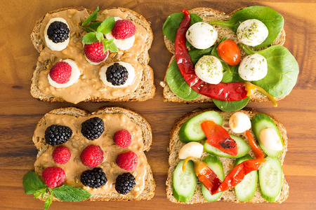 Four healthy open sandwiches for a picnic lunch topped with fresh berries, cheese, chili peppers, cucumber and baby spinach on wholewheat bread, overhead view on a wooden table
