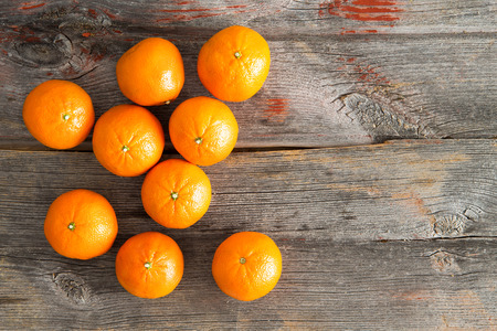 View from above of a group of delicious sweet juicy fresh clementines rich in vitamin C on a rustic wooden table with copyspace Фото со стока