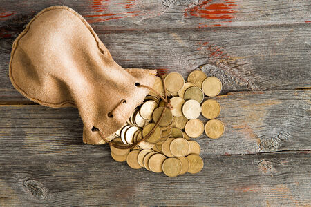 dollar coins: Pile of dollar coins spilling out of a drawstring pouch onto a rustic old weathered wooden table, view from above with copyspace Stock Photo