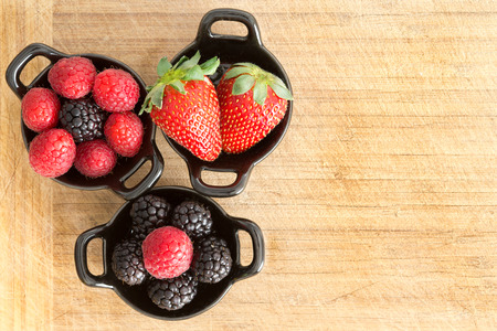 Overhead view of three ceramic ramekins full of healthy ripe fresh mixed berries including strawberries, blackberries and raspberries on a wooden surface with copyspace Reklamní fotografie