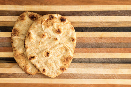 Crisp crusty naan whole grain flatbread that has been cooked in a traditional Indian tandoor clay oven served on a decorative striped wooden surface with copyspace