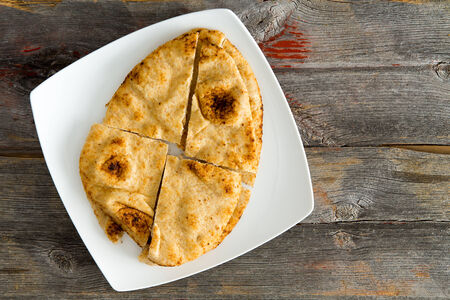 quartered: Overhead view of a crisp golden Naan flatbread baked in a traditional tandoor served on a modern square shaped white plate sliced into quarters on a rustic wooden table