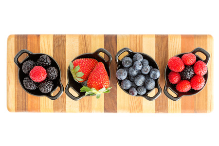 Selection of different ripe fresh autumn berries including strawberries, blueberries, blackberries and raspberries in separate dishes on a decorative striped wooden board, closeup overhead view
