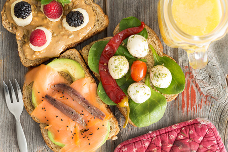 View from above of a selection of healthy picnic sandwiches topped with smoked salmon, anchovies, avocado, mozzarella, baby spinach, chili and fresh berries with a jug of orange juice 版權商用圖片