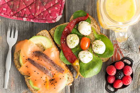 open topped: Delicious gourmet open sandwiches on wholewheat bread topped with smoked salmon, anchovies, avocado, mozzarella, baby spinach and chili pepper served on a picnic table with fresh berries