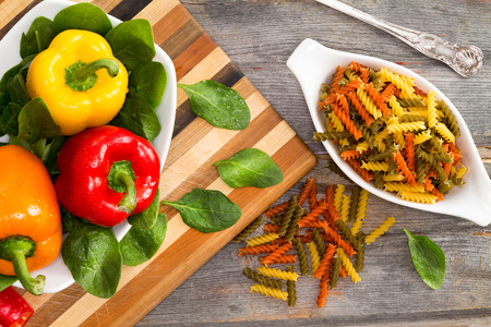 Ingredients for a delicious fusilli pasta with an overhead view of fresh colofrul sweet bell peppers in red yellow and orange on bed of baby spinach with dried corkscrews of tomato and spinach fusilli photo