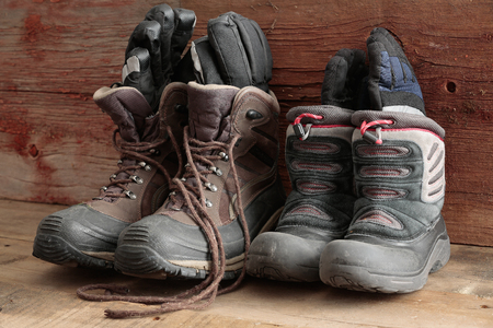 Adult and kids old winter snow boots with gloves inside them standing ready in a rustic wooden cabin to be worn outdoors in the freezing winter weather photo