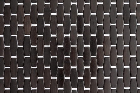 pliable: texture and pattern of a dark wood or bamboo mat with white cross weave detail and a repeat parallel pattern, close up detail in full frame coverage