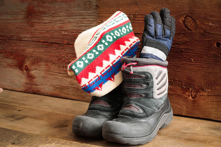scuffed: Childs snow boots with a colorful knitted winter cap and thick warm gloves standing ready in a rustic wooden cabin to venture out into the cold winter weather