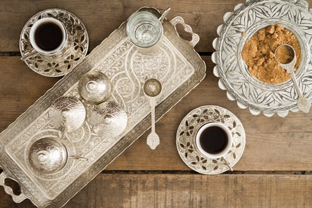Overhead view of a tray set with cezve for heating the pulverised or ground coffee beans and two cups of freshly brewed traditional Turkish coffee served with brown sugar photo
