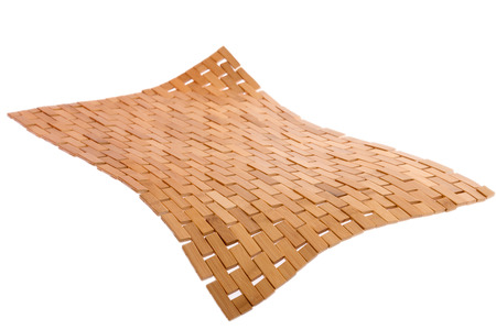 Whirling bamboo mat floating in the air isolated on white with a diagonal perspective and corner bent down in the foreground showing weave and texture detail photo