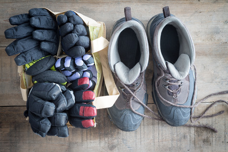 hardwearing: Snow boots with the laces lying free and a bag of winter gloves and mittens standing ready side by side on the floor of a rustic cabin, overhead view
