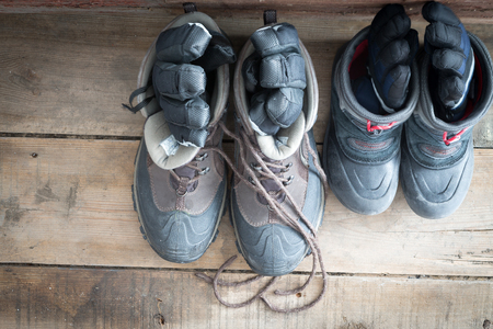 View from above of a pair of adult snow boots alongside those of a child on the wooden floor of a cabin each with a pair of gloves inside ready to be worn to go out into the cold winter weather
