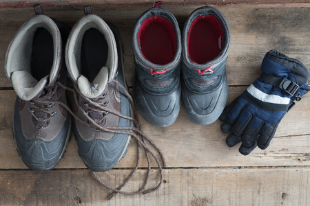 Overhead view of a pair of adult and kids snow boots standing ready on a rustic wooden floor alongside a pair if childs warm winter gloves to protect against the freezing cold weather, view from above photo
