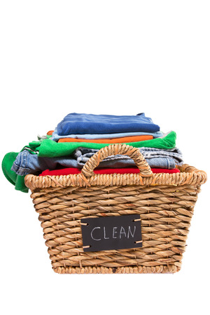Wicker laundry basket filled with stack of folded colorful clean clothes ready for ironing with a handwritten label on the side of the basket saying - Clean - end view isolated on white