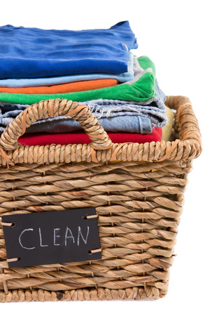 Close up view of washed fresh clean clothes neatly folded and stacked in a rustic wicker laundry basket with a handwritten label saying - clean - attached to the side, isolated on white photo