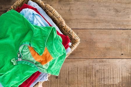 Čisté promytá unironed letní šaty s čerstvou vůní naskládaných v proutěném koši na prádlo s zářivě zelené tričko na vrcholu, zpětný pohled na rustikální dřevěné desky s copyspace na pravé straně Reklamní fotografie
