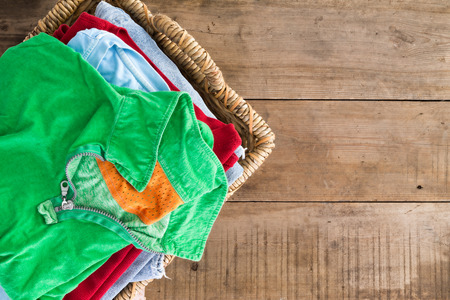 Clean washed unironed summer clothes with a fresh fragrance stacked in a wicker laundry basket with a bright green shirt on top, overhead view on rustic wooden boards with copyspace to the right photo