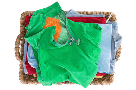 Clean fresh washed summer clothes in a basket neatly folded and viewed from above with a colorful green shirt on top of the pile, overhead close up view isolated on white photo