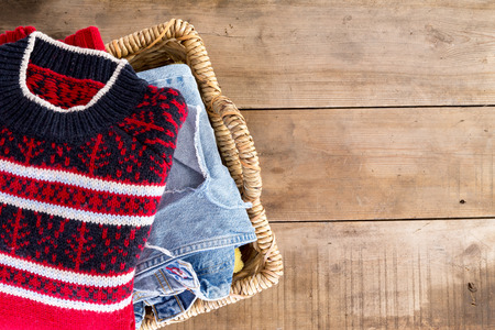 Wicker laundry basket filled with clean fresh washed winter clothes viewed from overhead standing at an angle on rustic wooden boards with copyspace on the right photo