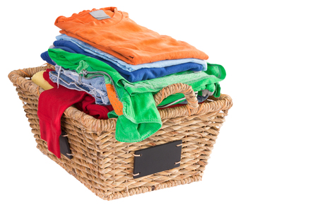Colorful collection of clean washed fresh summer clothes in a rustic woven wicker laundry basket with blank attached labels, high angle view isolated on white with copyspace to the right