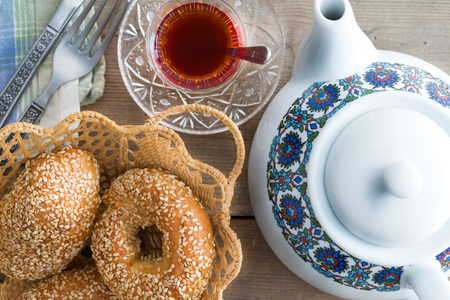 Close up view from above of crusty golden fresh Turkish sesame bagels served with a freshly brewed cup of tea and a teapot for teatime
