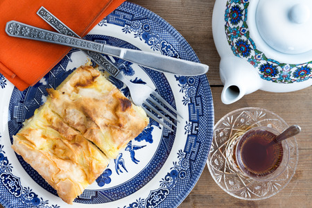 Delicious slice of homemade Turkish borek on a plate with cutlery served with a cup of freshly brewed Turkish tea and a teapot