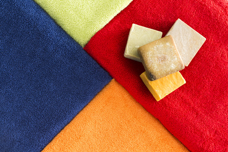 organic cotton: Vibrant colorful cotton bath towels arranged in an abutting geometric pattern with bars of herbal and organic soap for a relaxing aromatherapy spa treatment Stock Photo