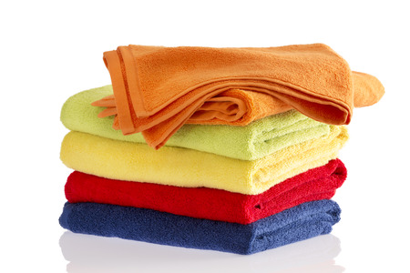 hand towel: Neatly folded stack of soft fluffy towels in the colors of the rainbow on a reflective white background with the top orange towel turned at an angle to the others Stock Photo