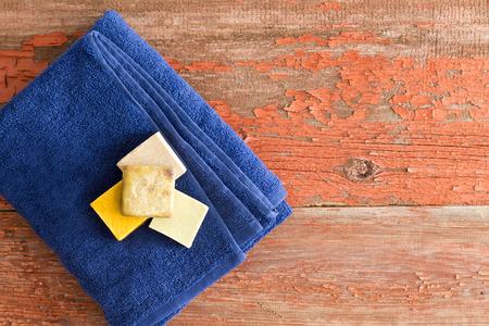 mimos: Jabones orgánicos sanos en una toalla azul suave cuidadosamente doblada sobre rústicas tablas de madera en un salón de spa y de belleza para un tratamiento de aromaterapia mimos