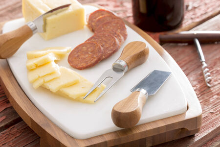 Harvati cheese with sliced spicy sausage served on a cheeseboard with cheese cutters alongside a bottle of red wine with a corkscrew