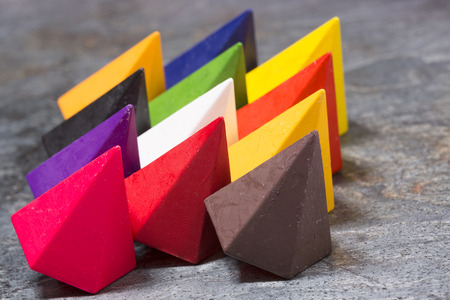 Vibrant multicolored diamond-shaped wax crayons in the colors of the rainbow arranged in three rows on a grey stone background, close up side view photo