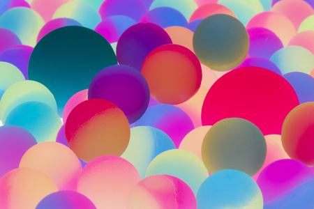 Illuminated bicolor balls background in the colors of the spectrum with a close up view of multiple balls of different sizes in a random pattern