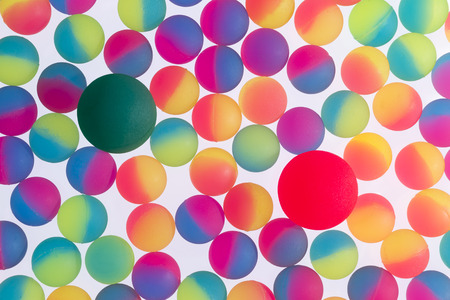 Colorful background of illuminated bicolor plastic balls in the colors of the rainbow arranged in a single full frame layer on a white background