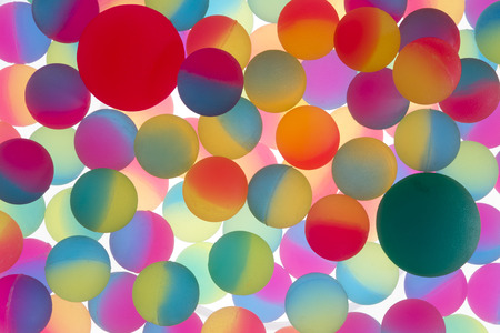 dichromatic: Colorful abstract background of illuminated bicolour plastic balls in the colors of the rainbow in a double layer and random arrangement on a white background , full frame Stock Photo