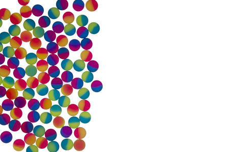 brightly colored: Border of illuminated brightly colored bicolor plastic balls arranged as a single layer to the left of the frame isolated on a white background with copyspace Stock Photo