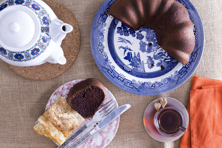 Turkish borek and chocolate cake served for tea with a traditional Turkish teapot and glass of tea on a neutral coloured mat, overhead view 写真素材