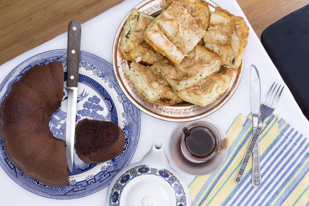 plateful: View from above of a plateful of flaky borek pastry and chocolate cake served at a party with a cup of traditional Turkish tea