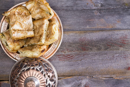 yufka: Portions of borek pastry served on a plate with a traditional silver metal dome set to one side on an old wooden rustic table with copyspace Stock Photo
